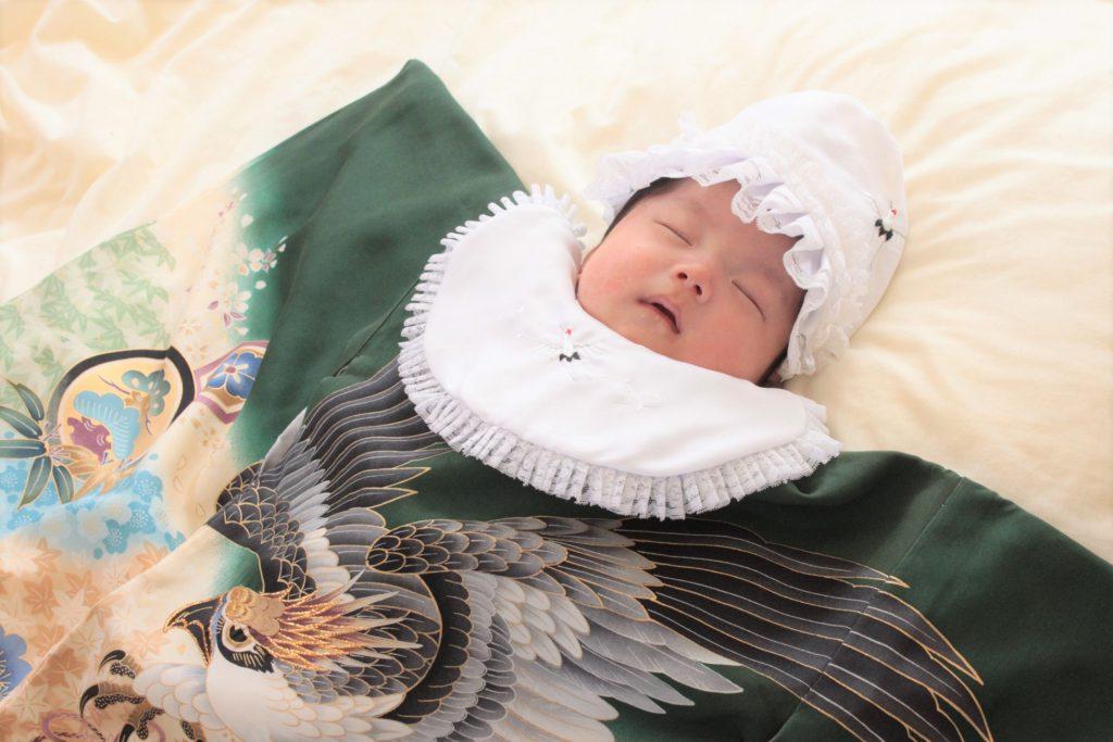 産着とお祝い着を着ている男の子の赤ちゃん